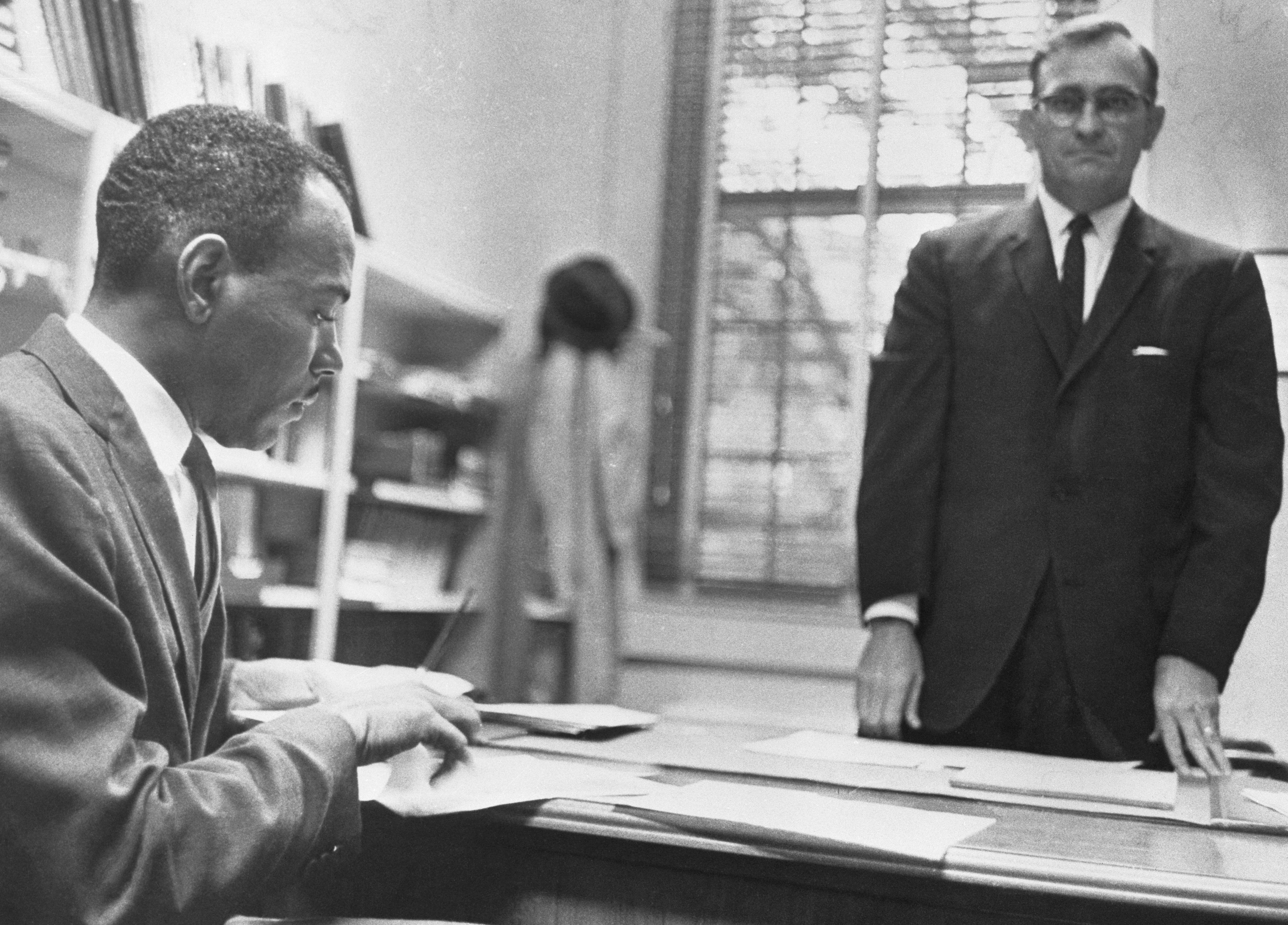 James Meredith signing registration papers at desk while man in glasses stands nearby.