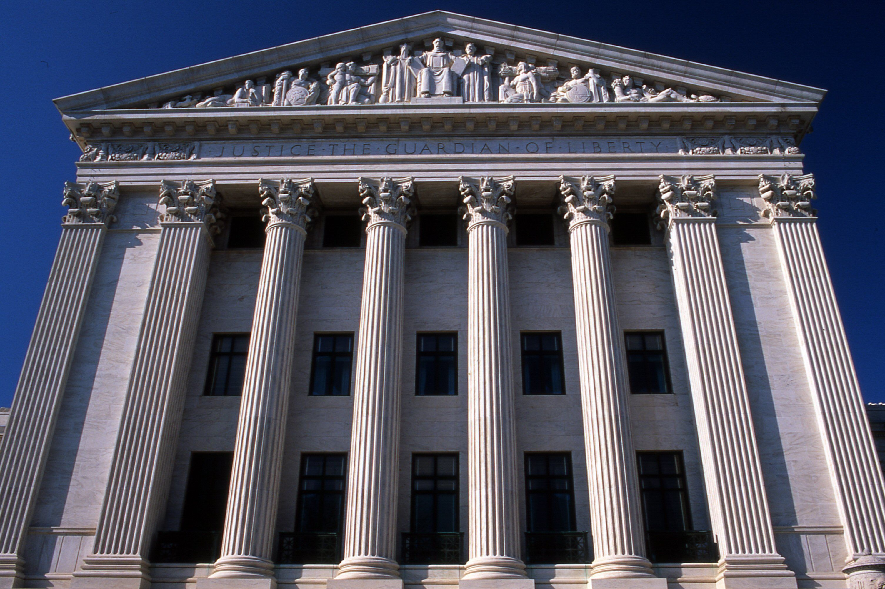 classical stone facade with four columns and two pilasters on each side, pediment of statuary