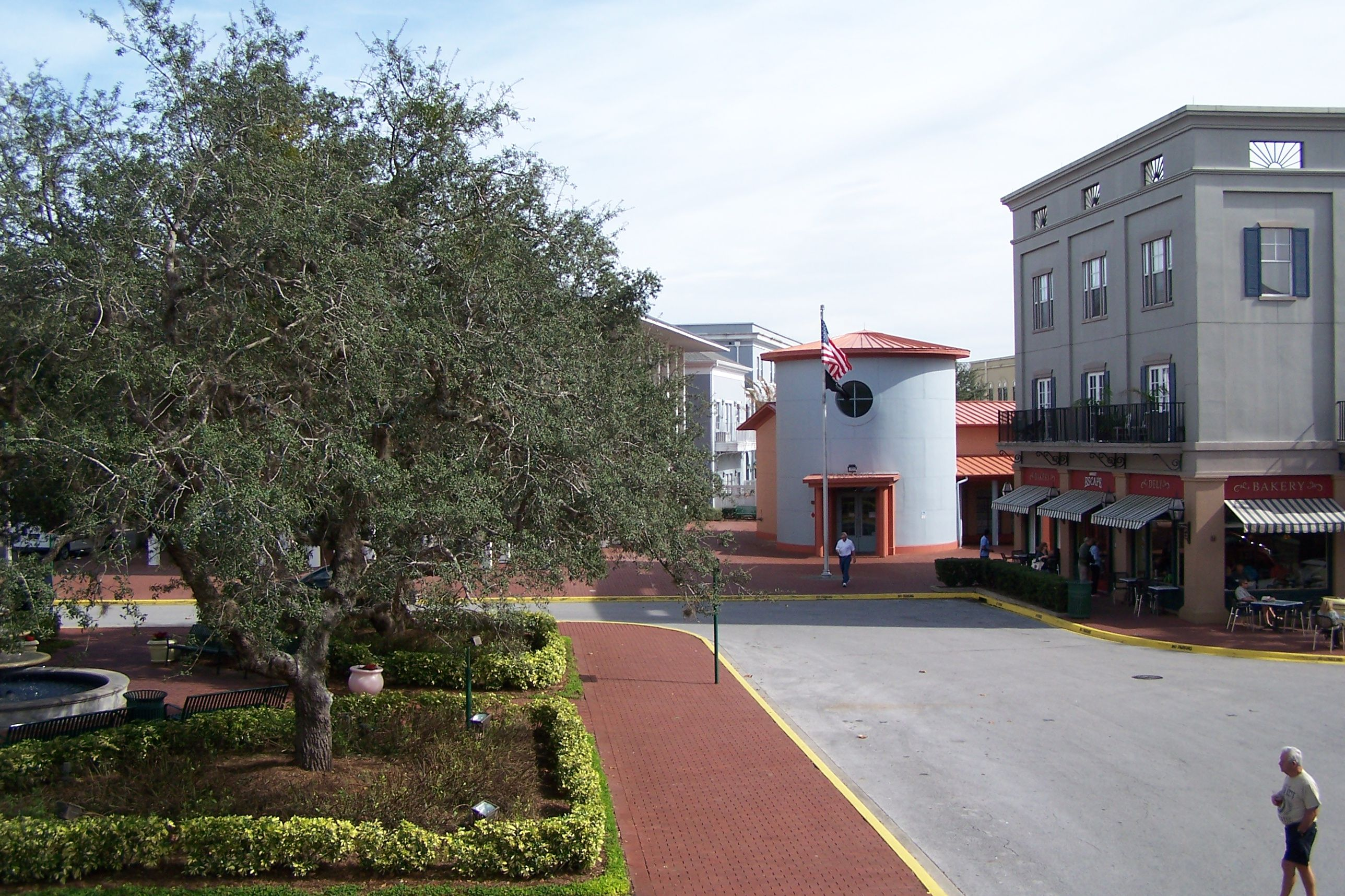 Plaza típica de la ciudad cerca de una oficina de correos cilíndrica y cafés en la acera bajo toldos