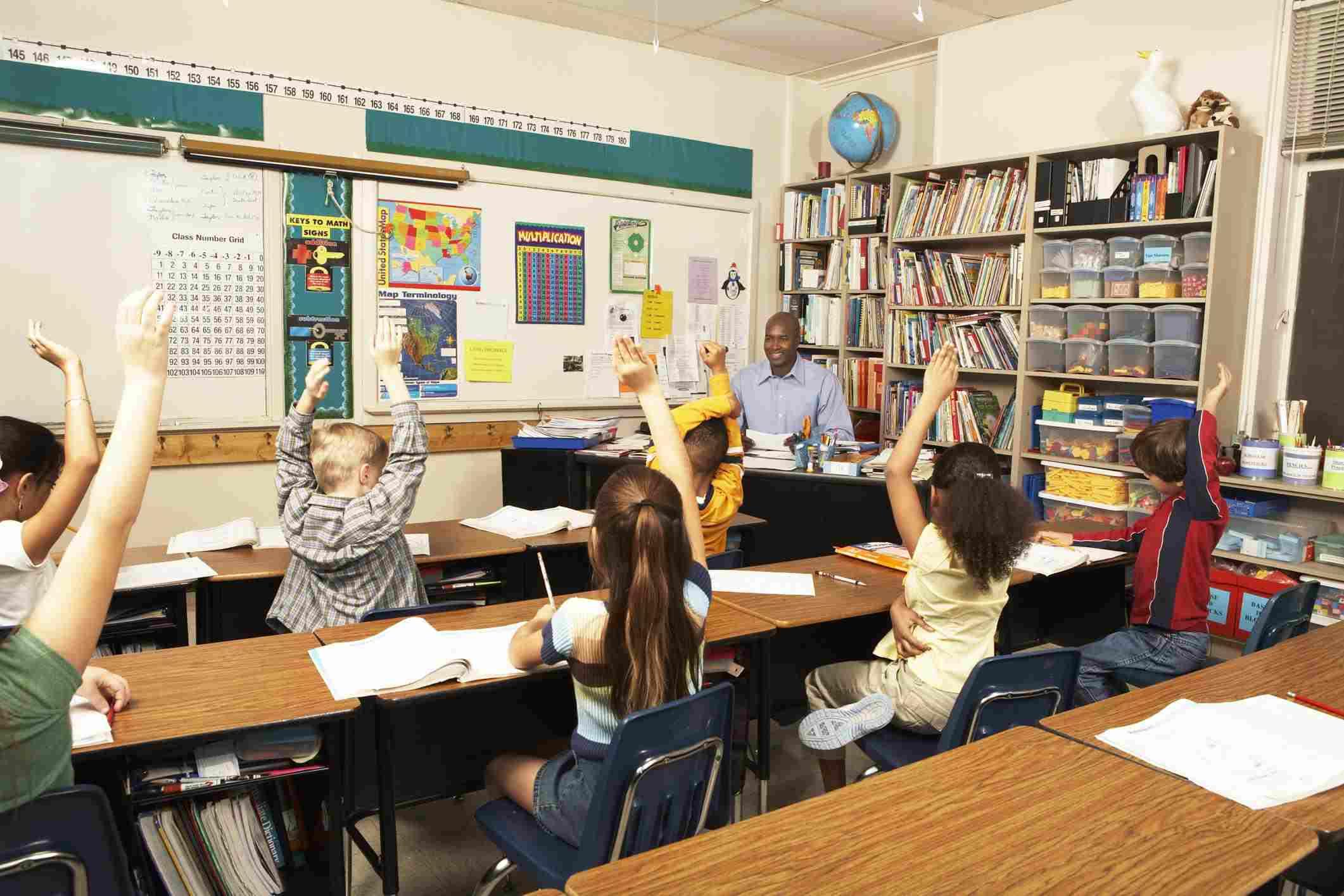 Schoolchildren raising hands for teacher in classroom