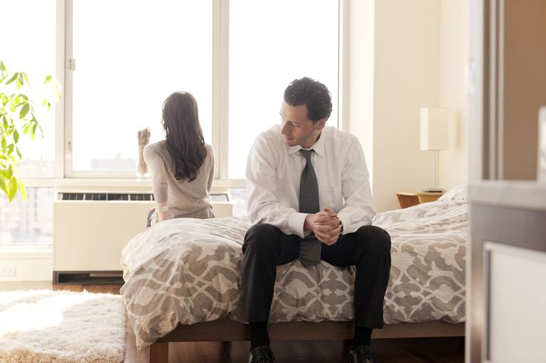 Couple Facing Away From Each Other On Bed
