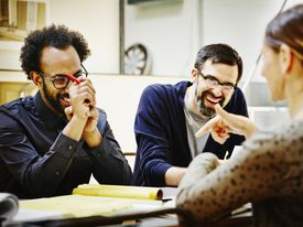 Laughing architects at conference table in office
