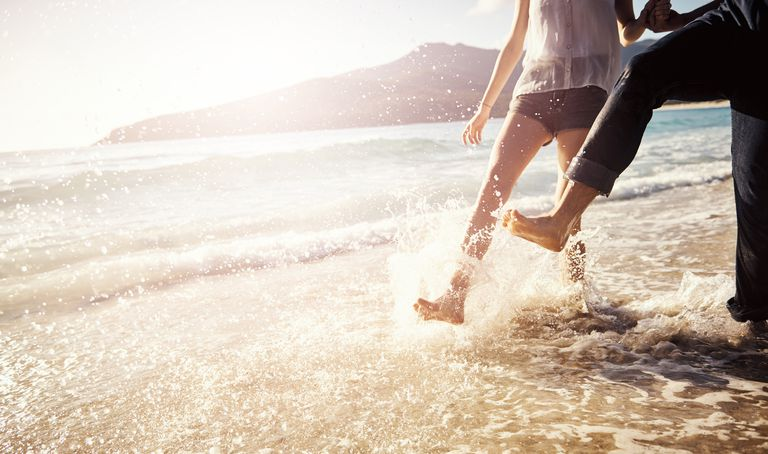 couple splashing in ocean water