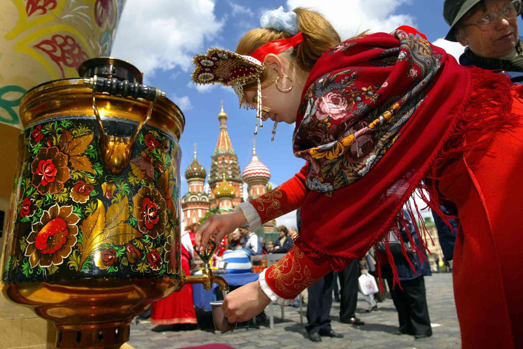 Russian girl wearing a traditional clothes pours water out of samovar