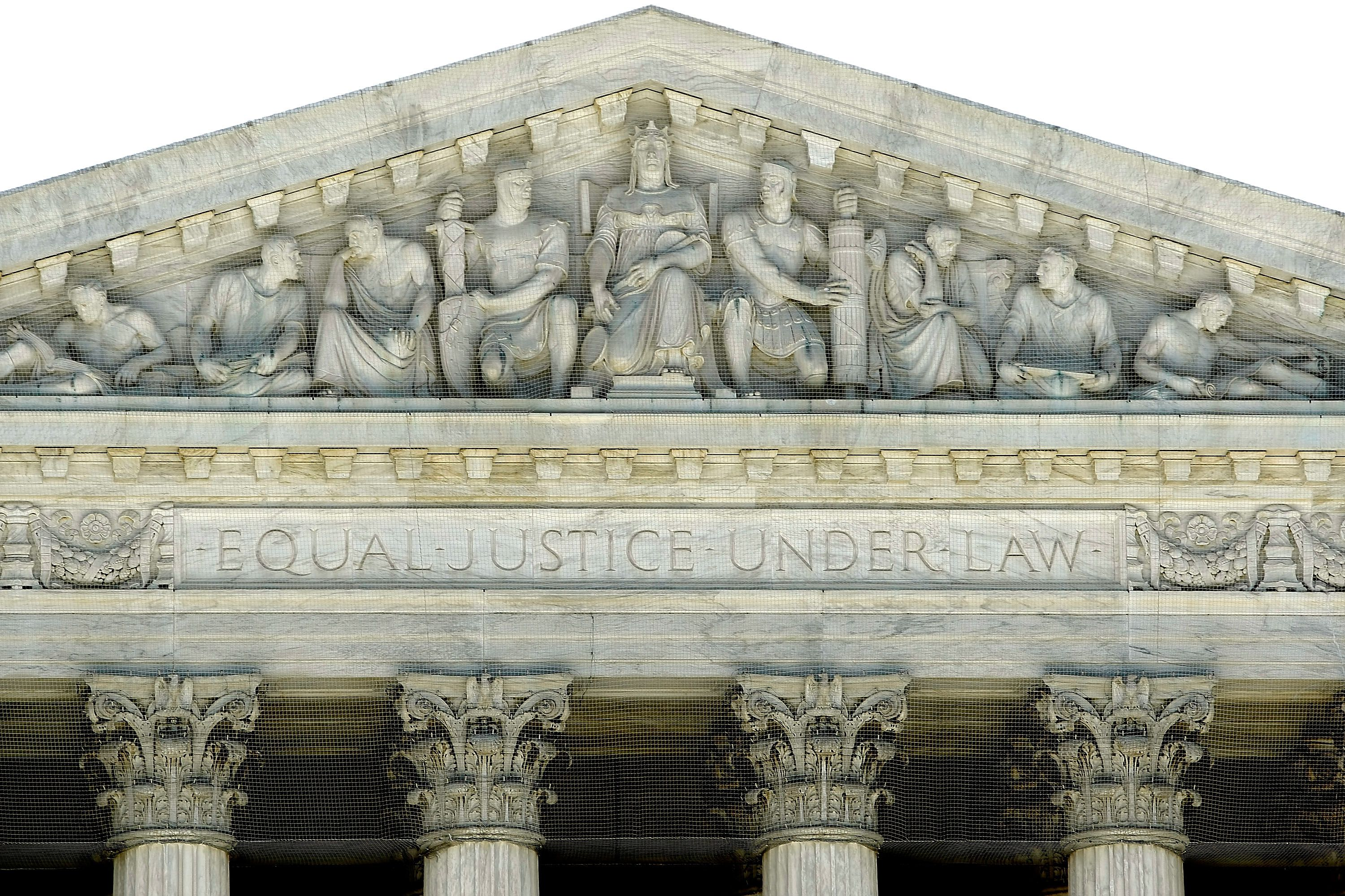 detail of sculptures tucked into a pediment above the words equal justice under the law and four capitals