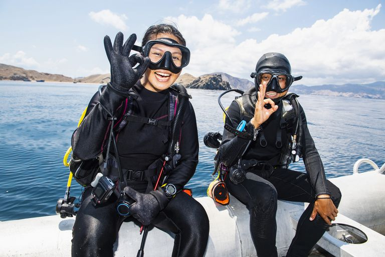 "Two scuba divers about to submerge into sea - giving the ""all ok"" hand signal, Komodo Island, East Nusa Tenggara, Indonesia"