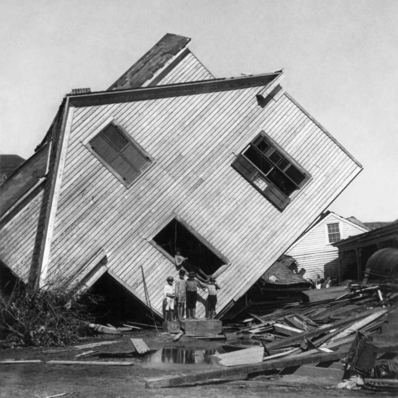 A house tipped on its side, with several boys standing in front, after the Great Galveston Storm in Texas.