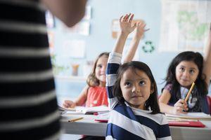 Little girl raising her hand in the classroom