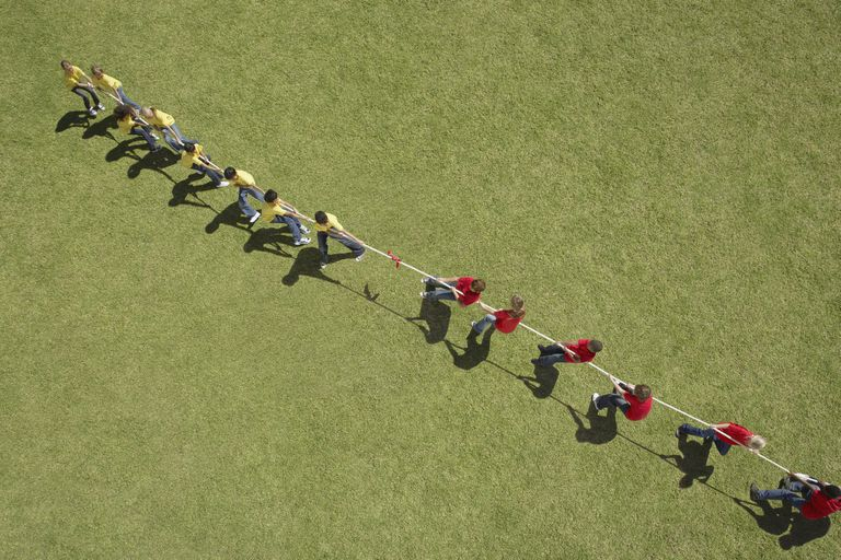 Two teams, one wearing red shirts and one wearing yellow shirts, compete in a game of tug of war.
