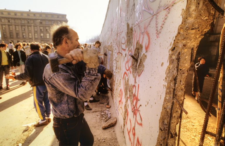 People hitting the Berlin Wall with hammers between Brandenburg Gate and Reichstag.