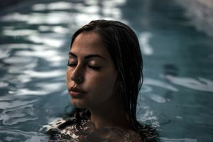Young woman floating upright in water with eyes closed.