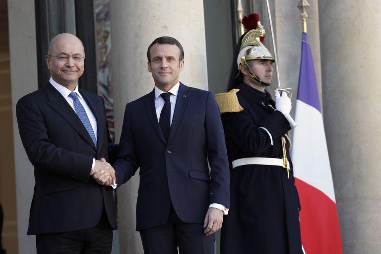Iraqi President Barham Salih shakes hands with French President Emmanuel Macron