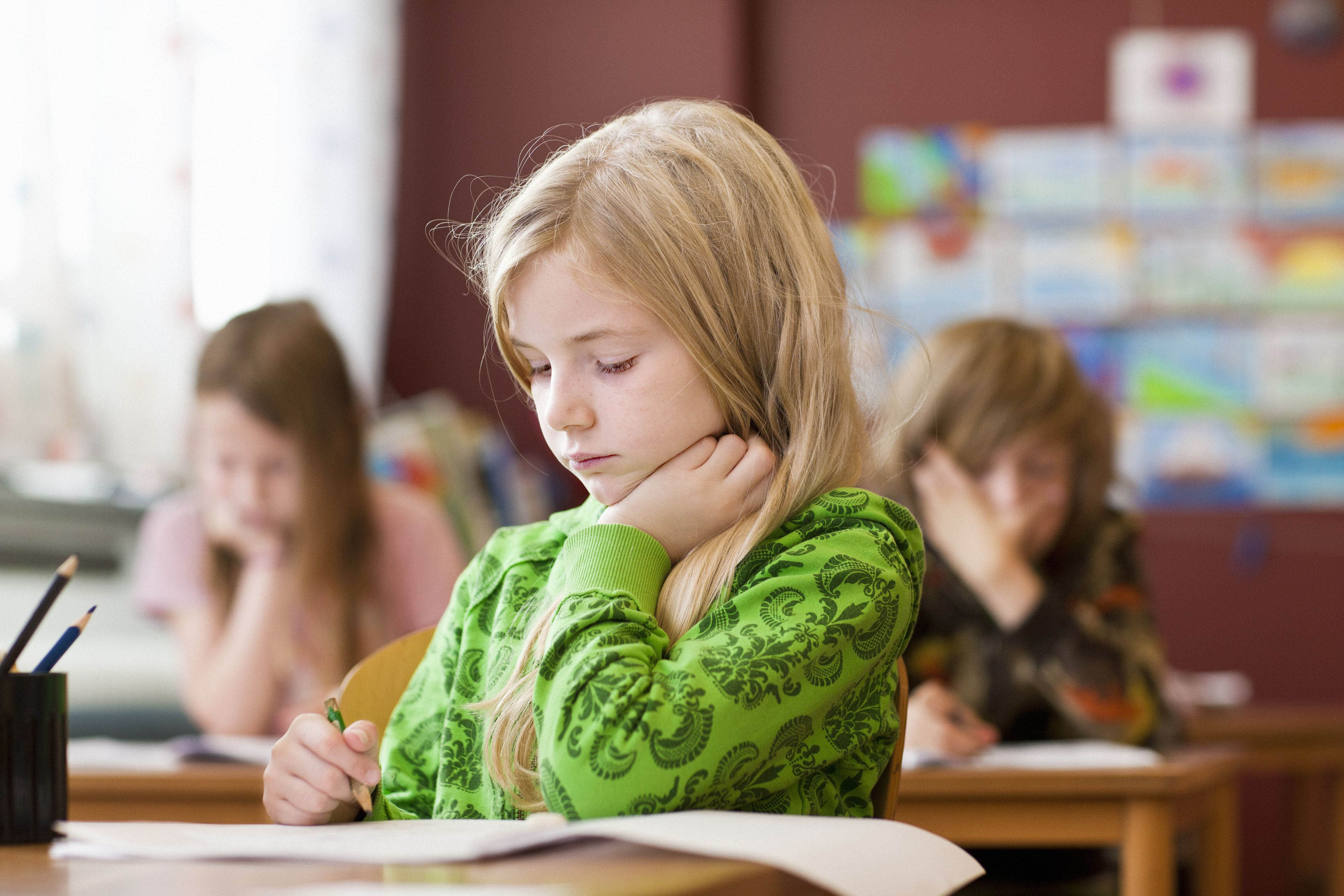 Schoolgirl writing in notebook at classroom