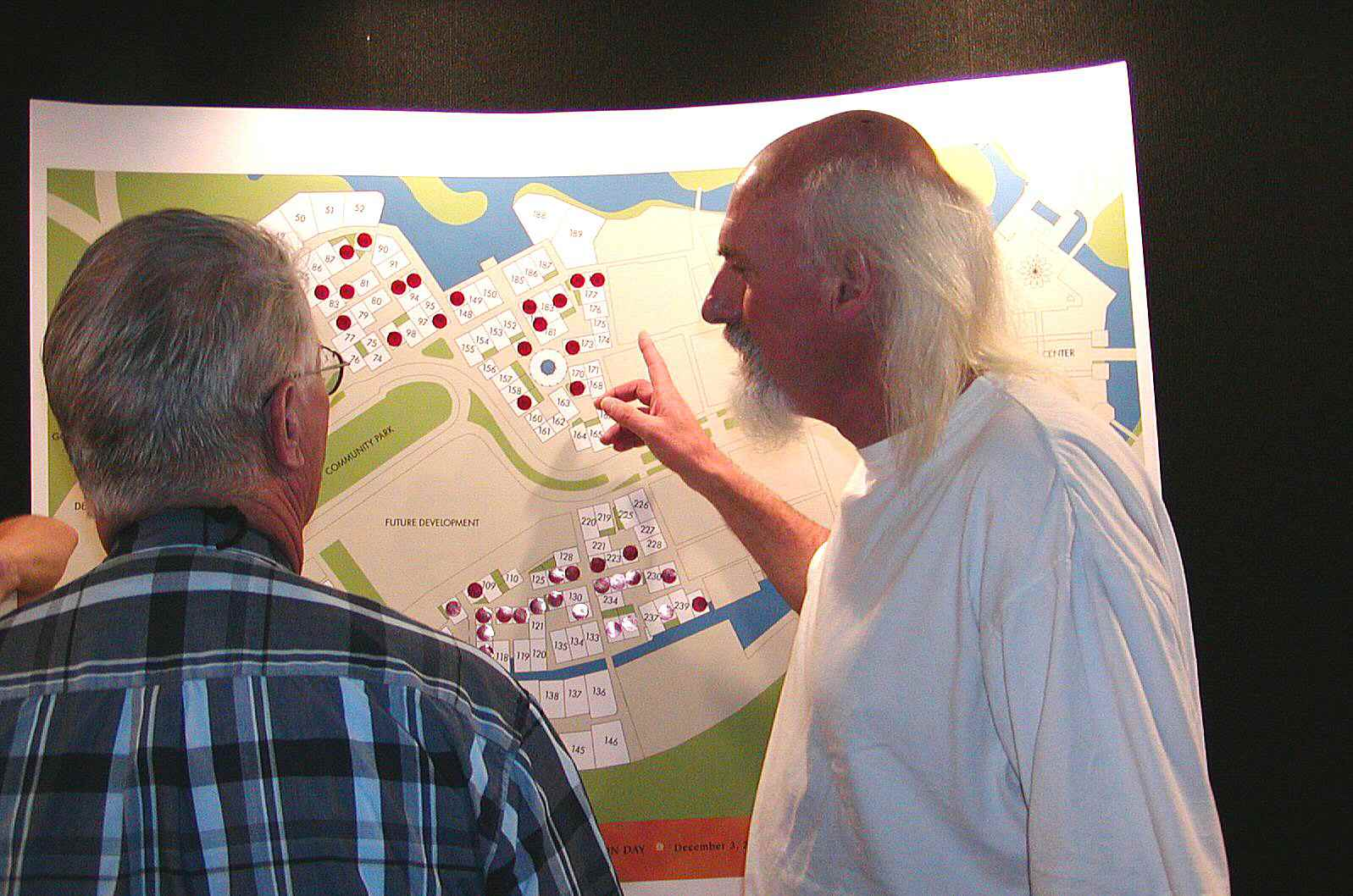 baldish man with scraggly white hair and beard explaining the urban layout to man in plaid shirt