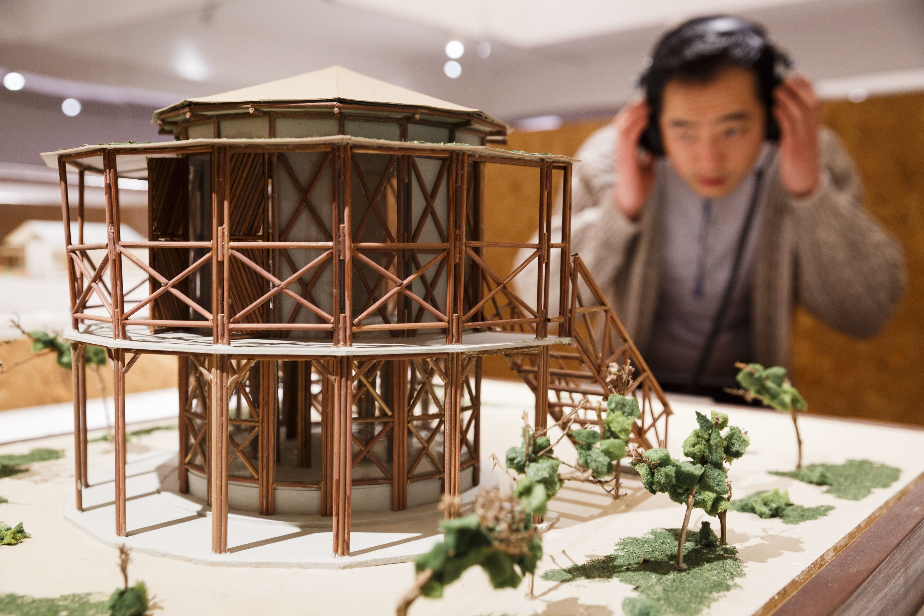 Model of round building with a young man examining it