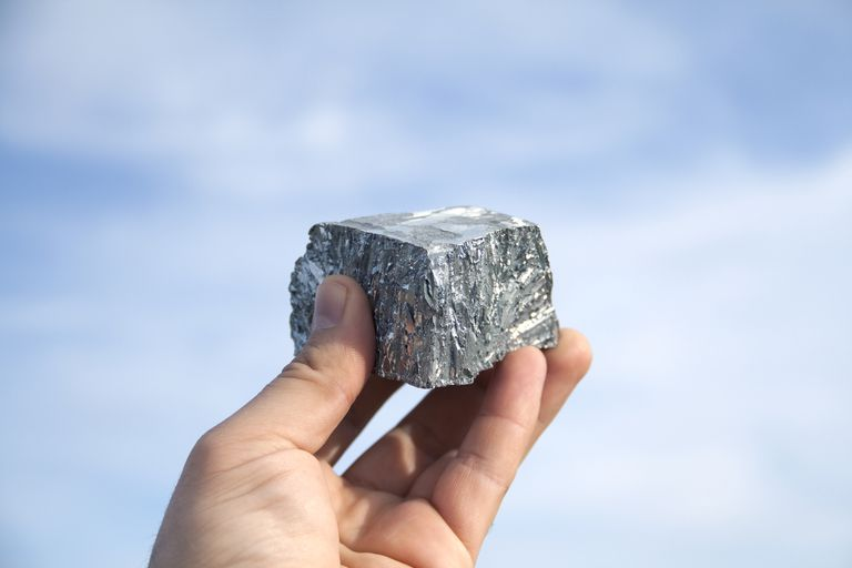 A nugget of zinc held up against a blue sky.