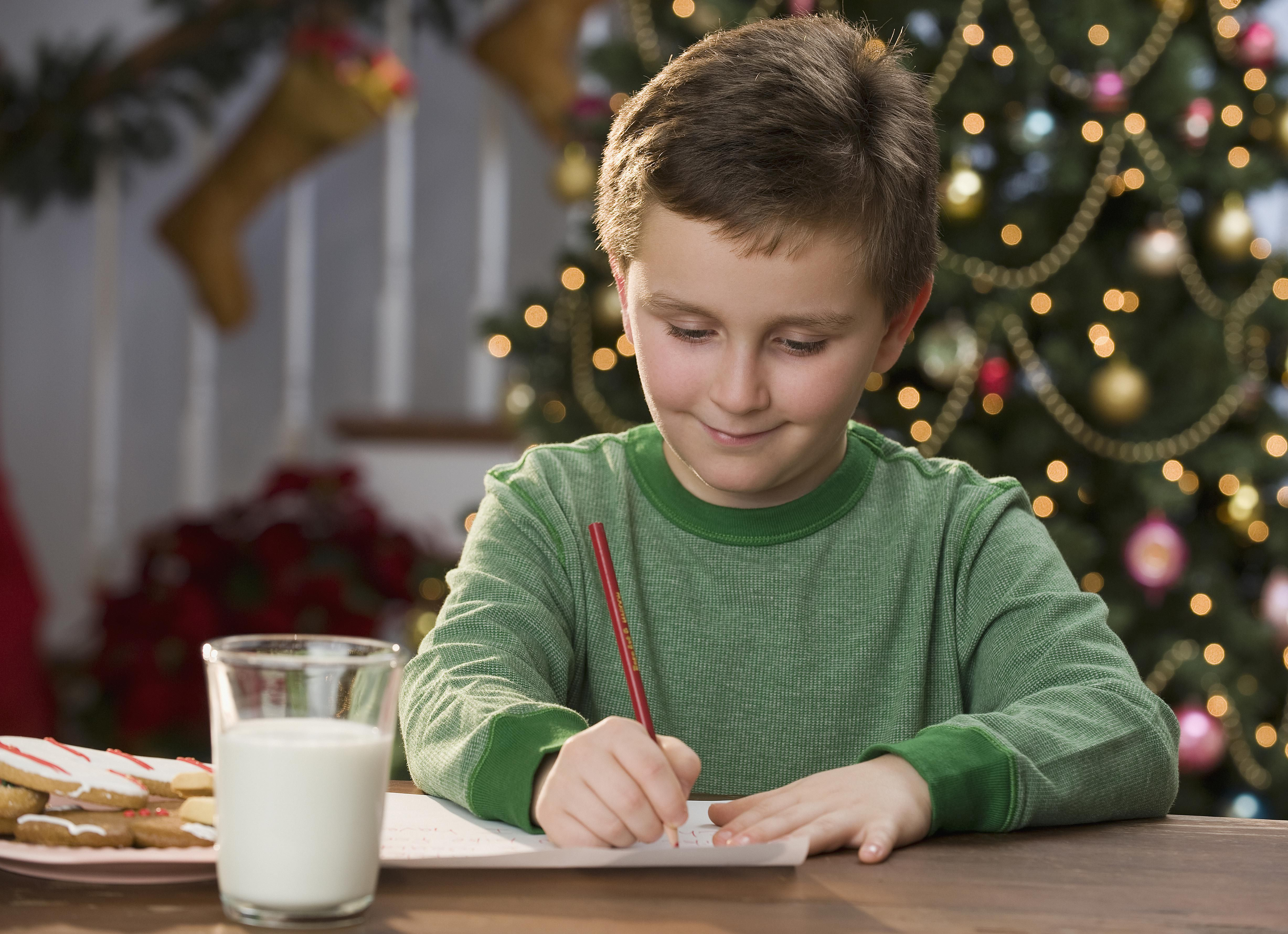 Boy writing letter in front of Christmas tree