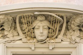 Art nouveau detailing, carved stone woman's face surrounded by stone flower petals and lyre-like details, in Prague, Czech Republic