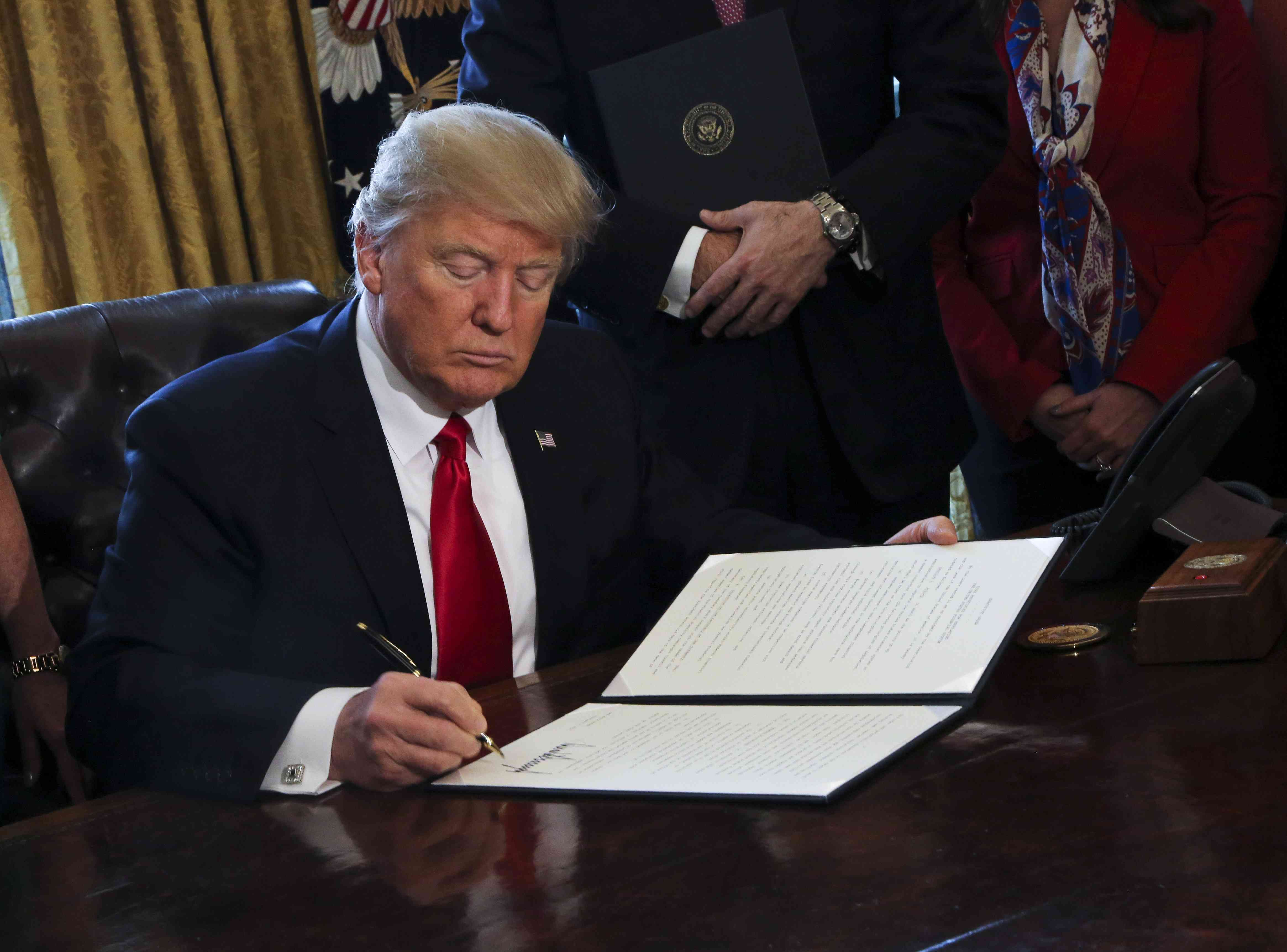 U.S. President Donald Trump signs Executive Orders, including an order to review the Dodd-Frank Wall Street to roll back financial regulations of the Obama era.
