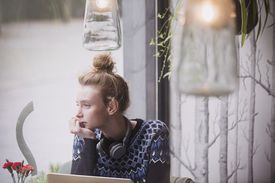 Pensive young woman with headphones at laptop looking out cafe window