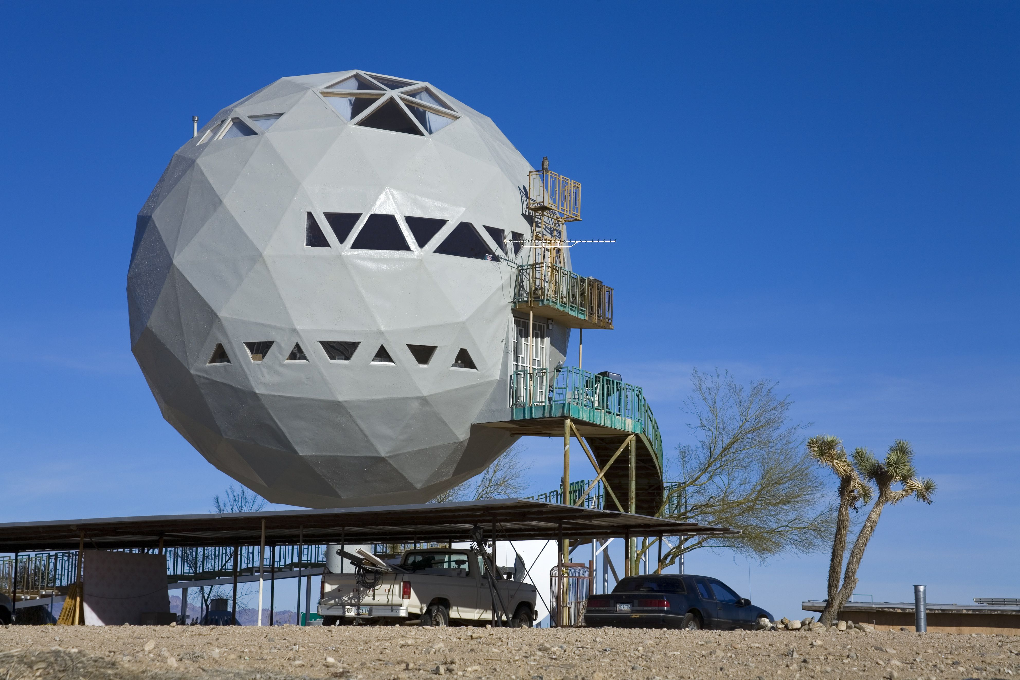 sphere on a platform with a car underneath and steps leading up to entrance points