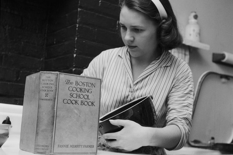 Priscilla Alden Kiefer, descendant of Priscilla Alden, studies Fannie Farmer's cookbook recipes, about 1955