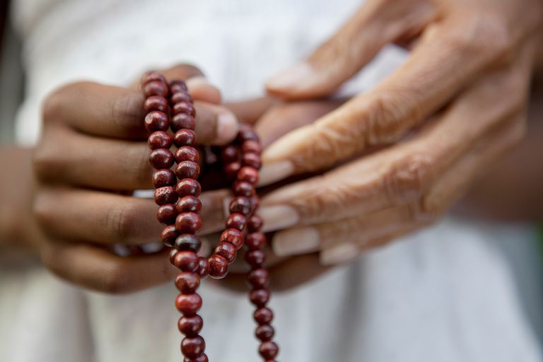 Close up of hands holding beads