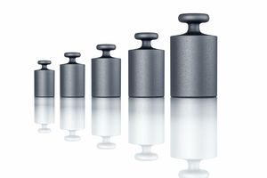 A series of grey metal weights on a white background