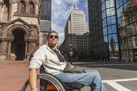 Woman in wheelchair at the John Hancock Tower and Trinity Church in Boston, Massachusetts