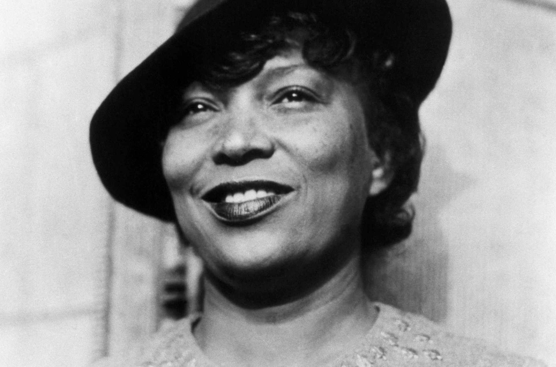 Zora Neale Hurston wearing a hat and smiling