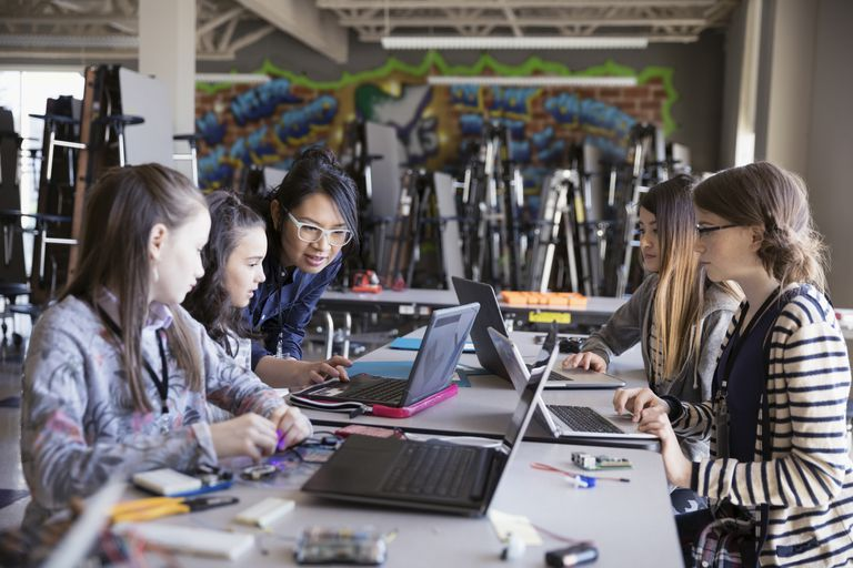 Female teacher helping pre-adolescent girls programming at laptops in classroom