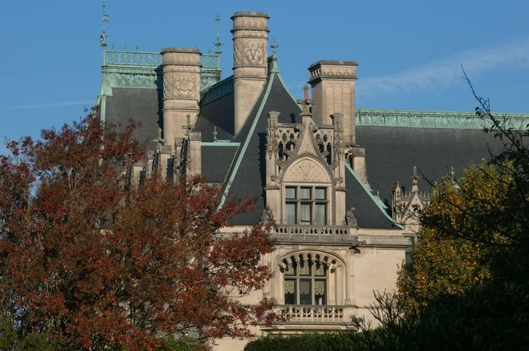 detail of chateau-like stone mansion with ornamentation, including three enormous chimneys