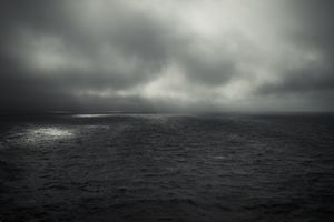 A gray cloud over gray waters
