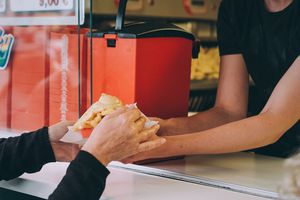 Man ordering french fries through a counter window