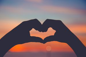 Silhouette of hands making a heart shape at sunset