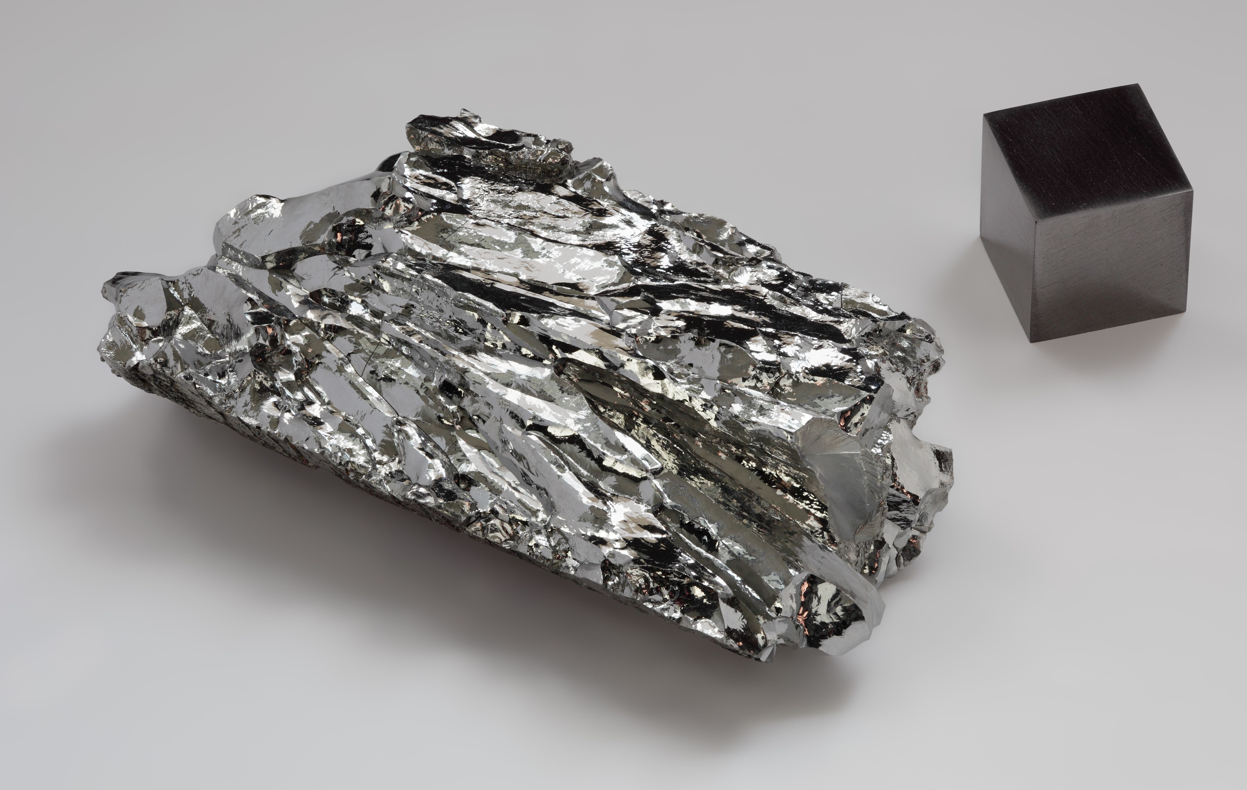 This is a photo of a piece of crystalline molybdenum and a cube of molybdenum metal.