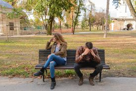 Woman and man on a bench in the park having an argument.