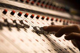Sound mixer pushing volume controls.