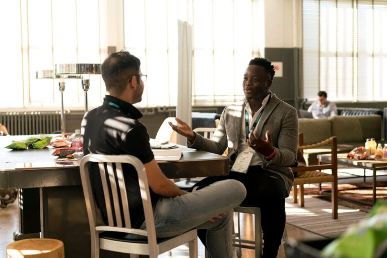 Two men having a conversation in a brightly-lit room.
