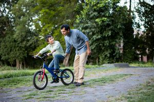 Latin father helping son on his bicyle