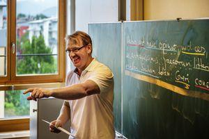 Male teacher (Latin) in front of blackboard