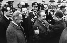 Brezhenev and al-Sadat greet each other with smiles surrounded officials and photographers