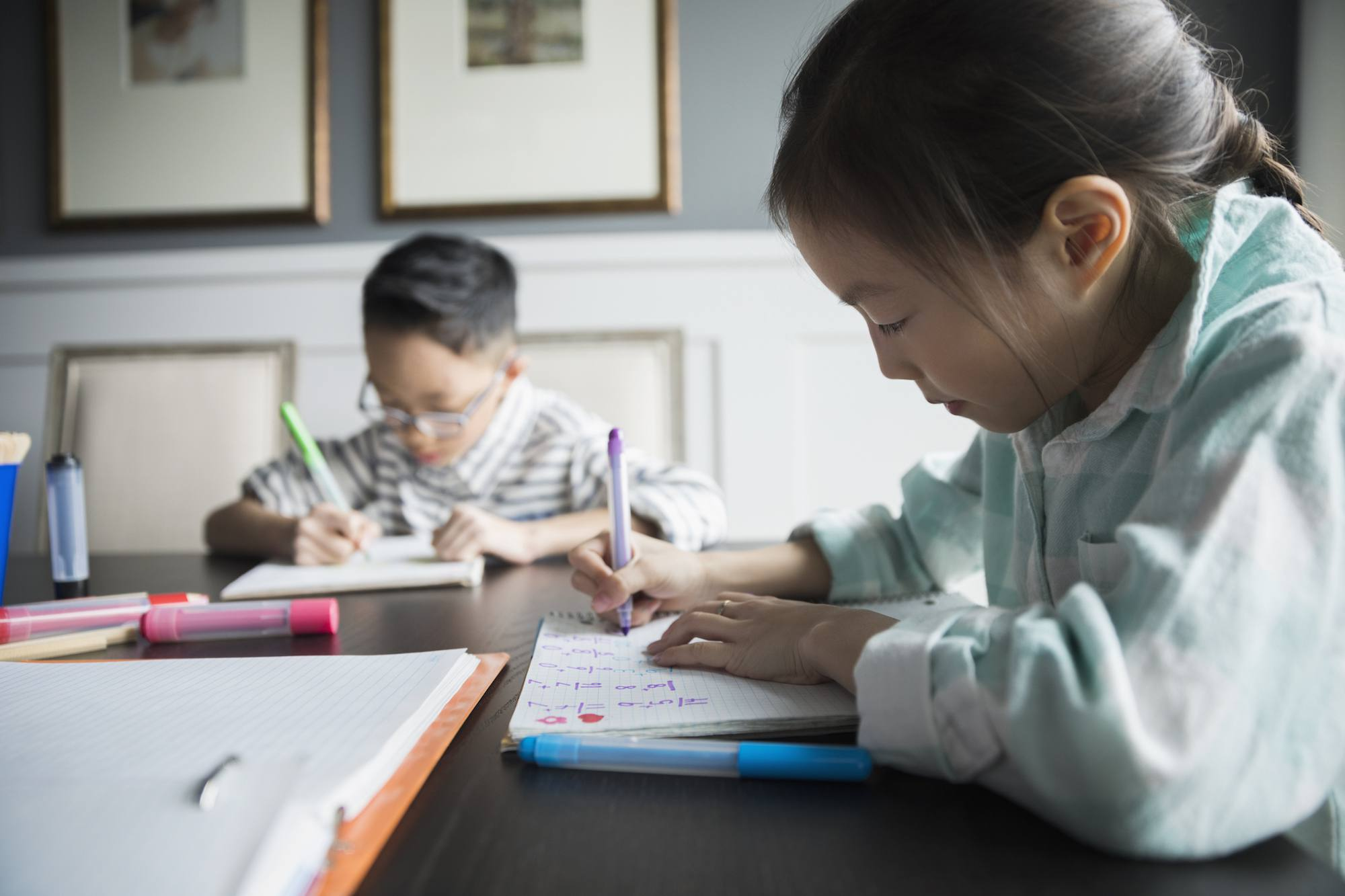 Brother and sister doing math homework with markers at table