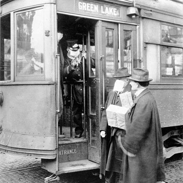A picture of a street car conductor not allowing passengers aboard without a mask.