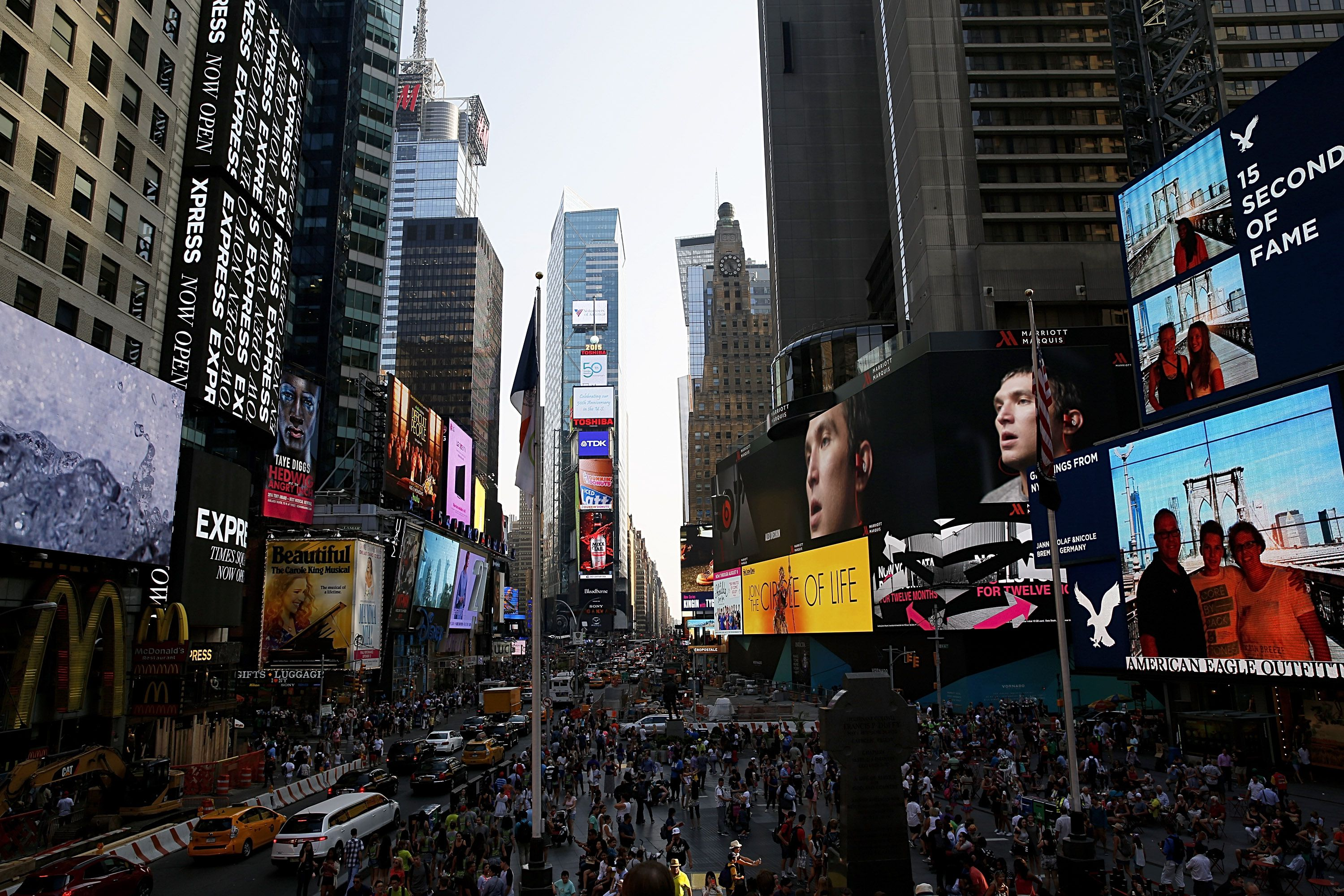 Pedestrians and tourists cross Times Square with it's various billboards on July 29, 2015 in New York City.