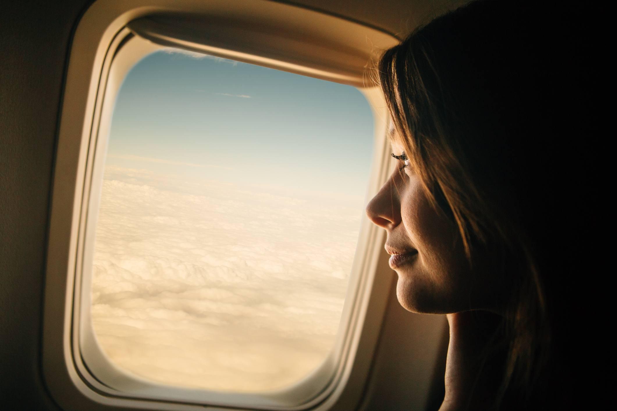 Mujer mirando por ventana de avión.