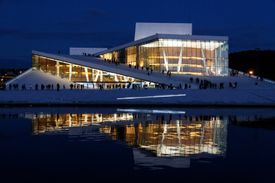 Nighttime view of lighted Oslo Opera House reflected in water