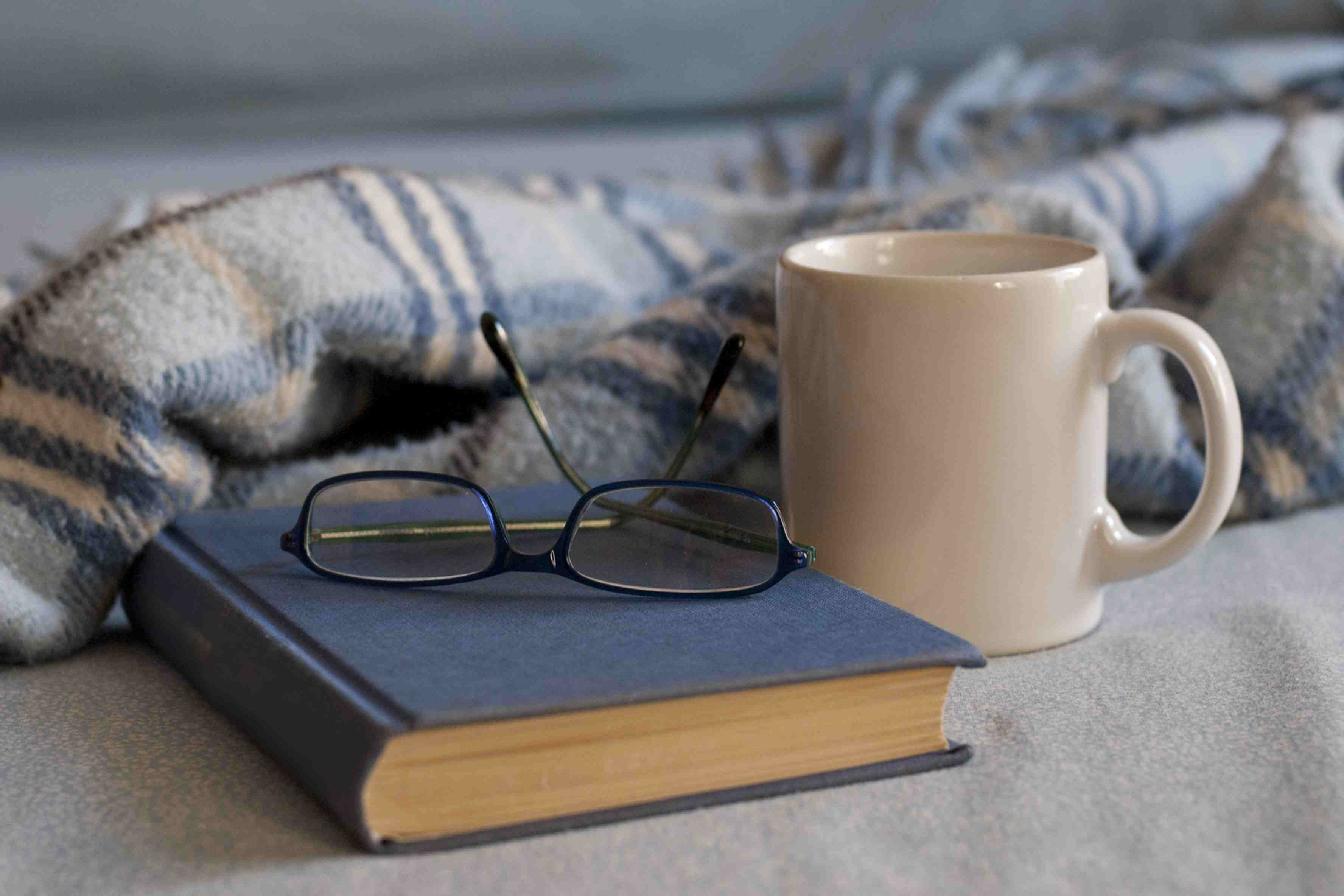 reading glasses on a book with a coffee mug and blanket