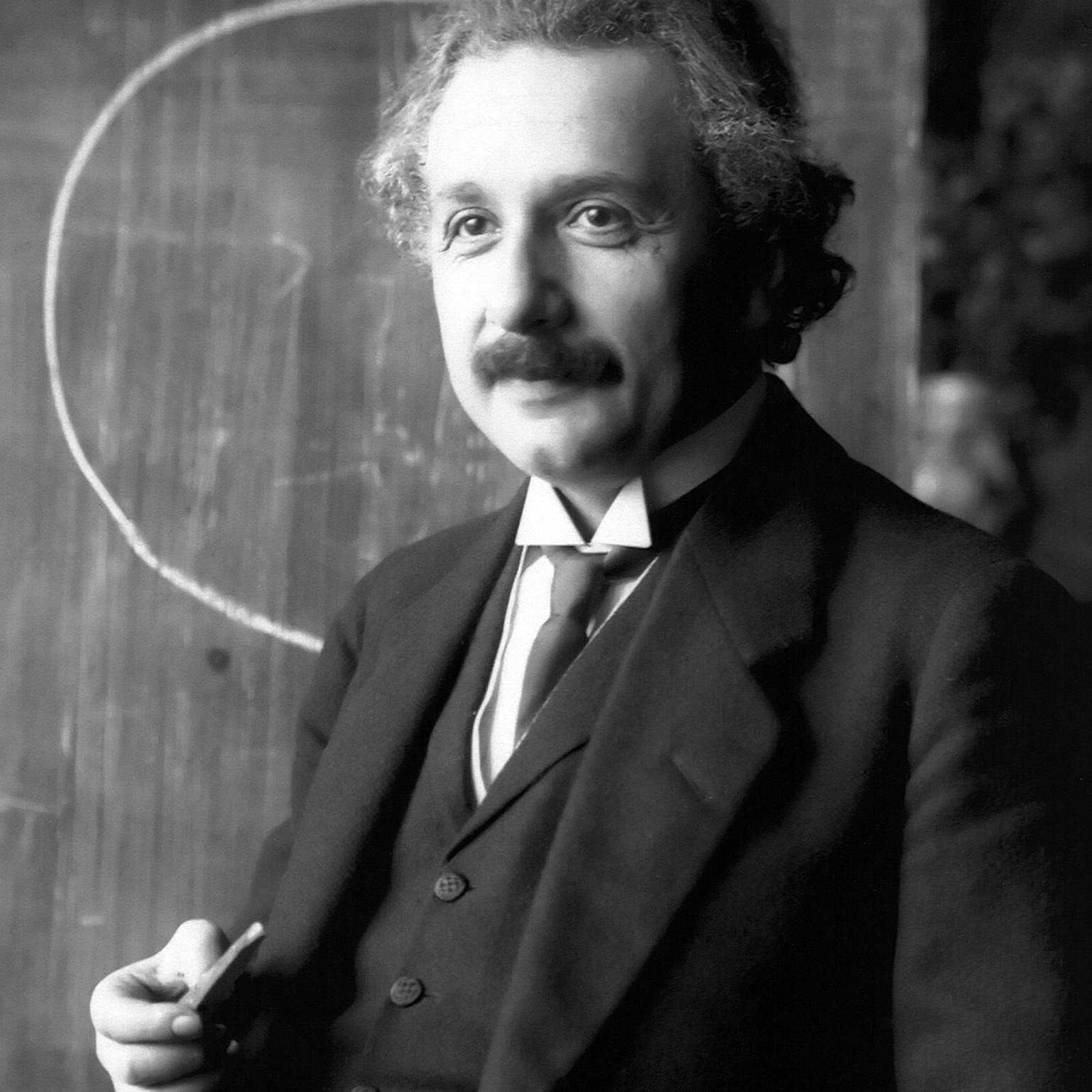 Black and white photograph of Albert Einstein in front of a blackboard.