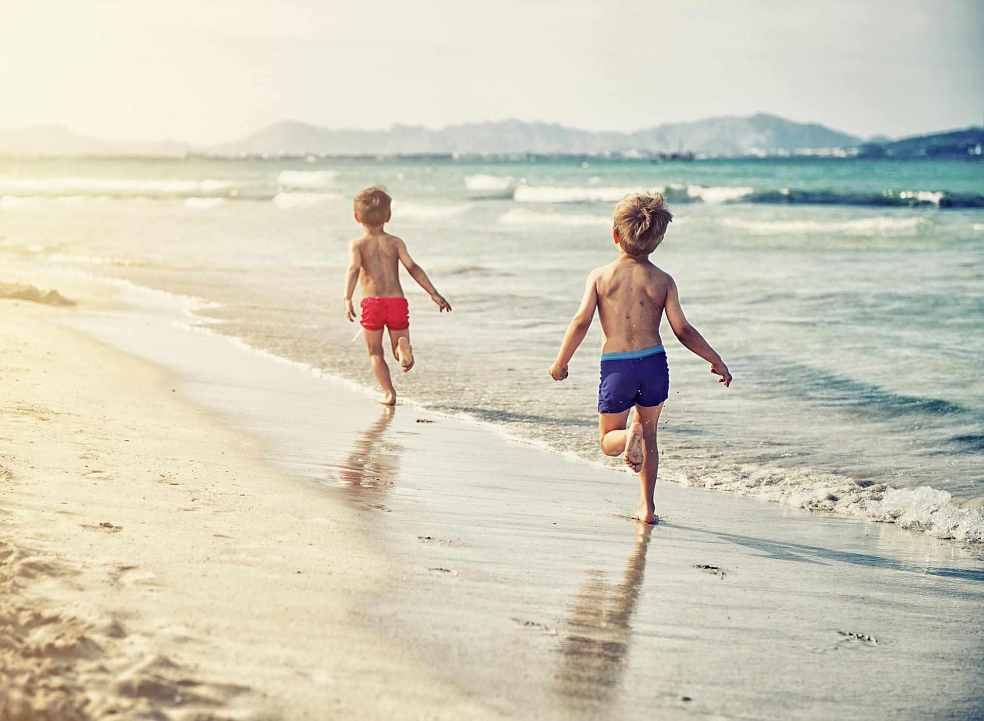 Niños corriendo a la orilla del mar